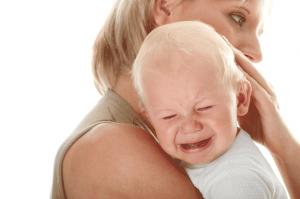 Фото: Ребенок капризничает и плачет на груди матери